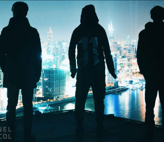 three hackers from behind looking at a city